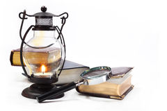 Still life with books. Books, magnifying glass and lamp with burning candle on white background Royalty Free Stock Image