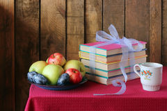 A still life with books, plums and apples. Plate with apples and plums and the books which are tied up by a blue tape lie on a table with a red cloth. A still Stock Photography