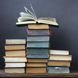 Still life with books. On a wooden table against a dark background Royalty Free Stock Images