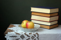 Still life with books. On a wooden table against a dark background Stock Images