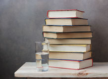 Still life with books. On a wooden table against a dark background Stock Photo