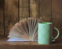Still life with books. On a wooden table against a dark background Stock Photos