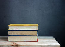 Still life with books. On a wooden table against a dark background Royalty Free Stock Photo