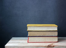 Still life with books. On a wooden table against a dark background Royalty Free Stock Photography