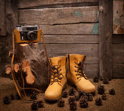 Still life with boots and retro camera on wooden Royalty Free Stock Photos