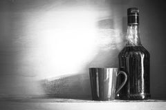 Still life of bottle of alcohol with cup on a shelve, vintage fi Royalty Free Stock Images