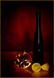 Still life of bottle and fruits on red old paper Royalty Free Stock Photos