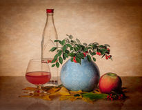 Still life with bottle, glass, and greenery Stock Images
