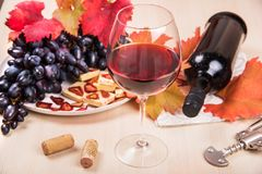 Still life with a bottle and a glass of red wine, grapes and chocolate with strawberries Royalty Free Stock Images