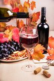 Still life with a bottle and a glass of red wine, grapes and chocolate with strawberries Stock Images