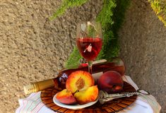 Still life with bottle,  glass of wine and peaches Stock Images