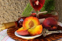 Still life with bottle,  glass of wine and peaches Stock Photos
