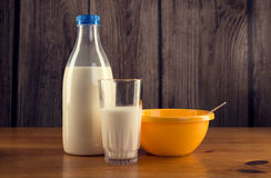 Still life of bottle of milk, glass of milk and yellow plastic bowl Royalty Free Stock Images