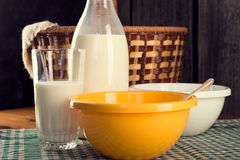 Still life of bottle of milk with glass and two plastic bowls Royalty Free Stock Images