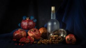 Still life with bottle, pomegranate and walnuts on hellouvin royalty free stock image
