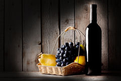 Still life with a bottle wine and  basket of fruit Royalty Free Stock Images