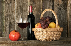 Still-life. Bottle of wine, glass and basket with fruit. Still-life. Bottle of red wine, glass and basket with fruit stock image