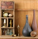 Still-life with bottles. Old shelf with subjects on a wooden background stock image