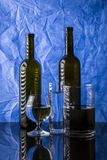 Still life with bottles and glasses with liquid. On blue background royalty free stock images