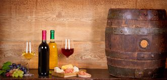 Still life with bottles and glasses of red and white wine with cheese, prosciutto and grape in wine cellar, old wine barrel. Food and drinks concept royalty free stock photos