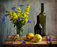 Still life with a bottles by lemons and flowers Royalty Free Stock Photos