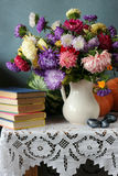 Still life with the bouquet of asters. Plums, pumpkins, a water-melon and books located on a table on a white cloth with laces against a blue wall Stock Photography