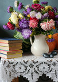 Still life with the bouquet of asters. Plums, pumpkins, a water-melon and books located on a table on a white cloth with laces against a blue wall Royalty Free Stock Images