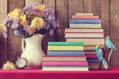 Still life with a bouquet of autumn flowers and books. Still life with a bouquet of autumn flowers, books and a alarm clock on a table with a red cloth. Back to Stock Photo