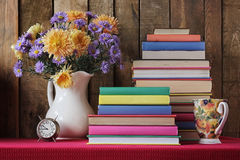 Still life with a bouquet of autumn flowers and books. Still life with a bouquet of autumn flowers, books and a glass on a table with a red cloth. Back to Royalty Free Stock Photo