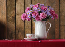 Still life with a bouquet of autumn flowers and a retro a cup. Stock Images