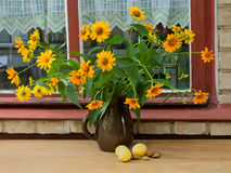 Still life - bouquet of bright yellow flowers on the wooden tabl. Still life - bouquet of bright yellow flowers and apricots on the wooden table against window Royalty Free Stock Image