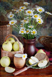 Still life with bouquet of camomile in a vase and apples Stock Photos