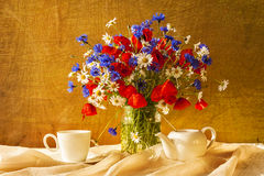 Still life bouquet camomiles cornflowers poppies Stock Photos