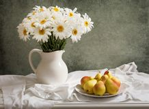 Still life with bouquet of daisy flowers in a jar and fresh pear royalty free stock images