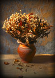Still life with bouquet of dried roses in clay vase Stock Photos