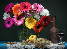 Still life with a bouquet, fruit and red wine. Transvaal daisies Stock Photography