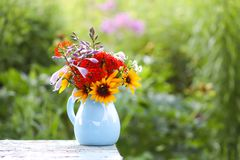 Still life with bouquet of garden flowers in a blue ceramics vase on the table outdoors. Still life with a bouquet of garden flowers in a blue ceramics vase on stock photo