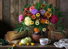Still life with a bouquet of garden flowers and fruit. Stock Image