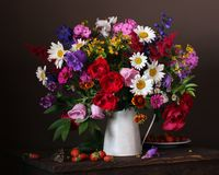 Still life with a bouquet of garden flowers in a jug. royalty free stock images
