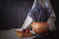 Still life with a bouquet of lavender, a book and plums on the table. stock photo