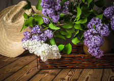 Still-life with a bouquet of lilacs and a straw hat Stock Photos