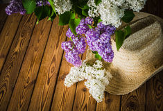 Still-life with a bouquet of lilacs and a straw hat Royalty Free Stock Images