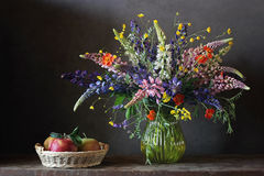 Still life bouquet with lupine and buttercups in a glass vase. Royalty Free Stock Image