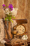 Still life bouquet. Still life with phlox bouquet in a vintage vase on the old chair with antique clock and oil lamp Royalty Free Stock Photos