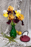 Still life. Bouquet with rare yellow and brown irises and tea pot Royalty Free Stock Photo