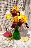 Still life. Bouquet with rare yellow and brown irises and tea pot Stock Photos