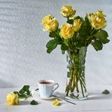 Still life with a bouquet of roses and a Cup of tea stock photography