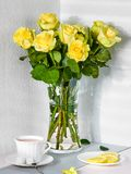 Still life with a bouquet of yellow roses and a Cup of tea stock photo