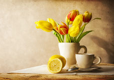 Still life bouquet yellow tulips cup of tea Royalty Free Stock Image