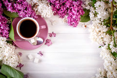 Still life with branches of lilac and a Cup of coffee on a wooden table. Royalty Free Stock Photography